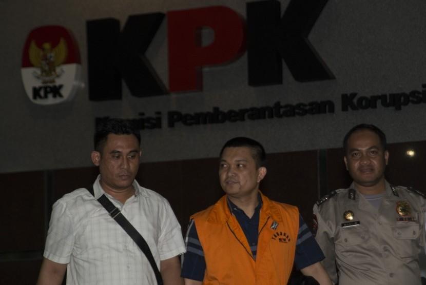 Anggota DPR Komisi XI dari Fraksi Partai Golkar Aditya Moha (tengah) berjalan keluar menggunakan rompi tahanan usai diperiksa di gedung KPK, Jakarta, Ahad (8/10) dini hari.
