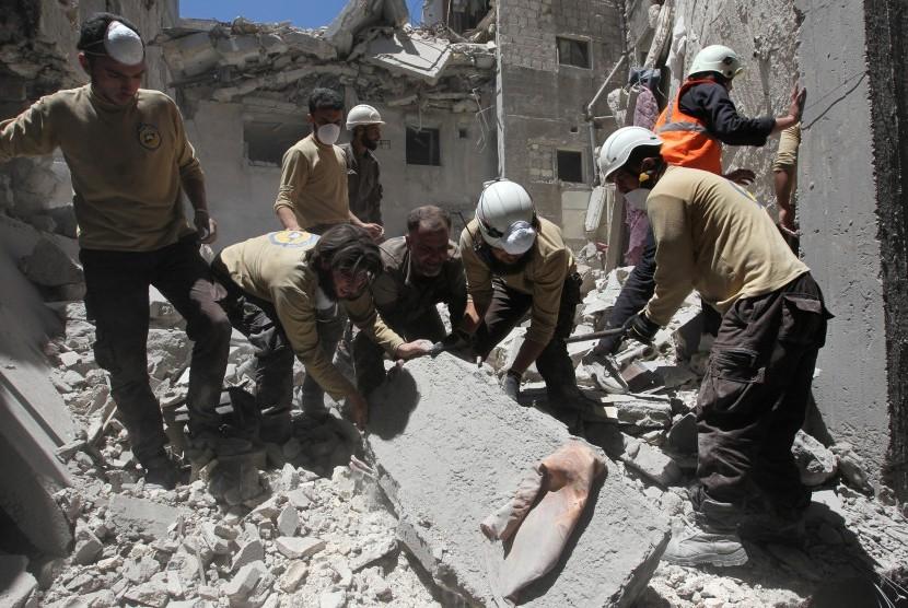 Anggota pertahanan sipil mencari para korban selamat setelah terjadinya aksi bombardir di Provinsi Idlib