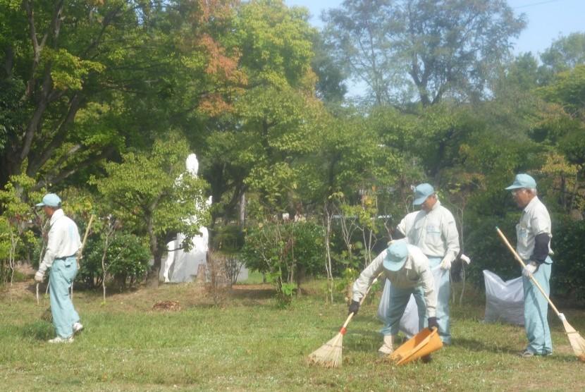 Anggota 'Sakai Silver Center' bekerja membersihkan Taman Daisen, Sakai, Jepang, Jumat (10/10).