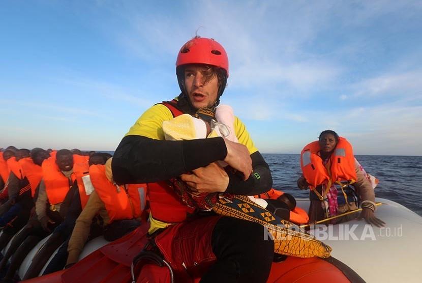 Anggota tim pertolongan dari Spanyol Daniel Calvelo menggendong bayi pengungsi berumur 4 hari dalam perasi SAR yang dilakukan LSM Spanyol di Laut Mediterania 22 mil laut utara Kota Sabratha, Libya (Ilustrasi)