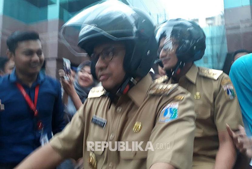 Anies-Sandi kembali ke kediaman mengendarai sepeda motor setelah mengunjungi projek underpass Mampang-Kuningan, Selasa (17/10).