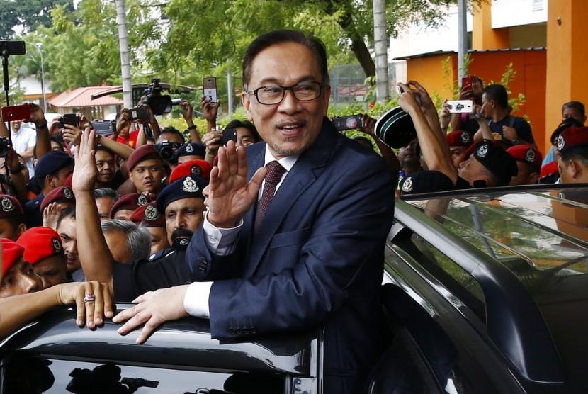 Anwar Ibrahim melambaikan tangan saat dinyatakan bebas seusai keluar dari rumah saki, Rabu (16/5).