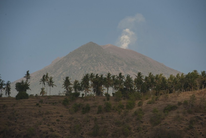 Asap mengepul dari kawah Gunung Agung yang berstatus awas terlihat dari Desa Amed, Karangasem, Bali, Jumat (29/9).