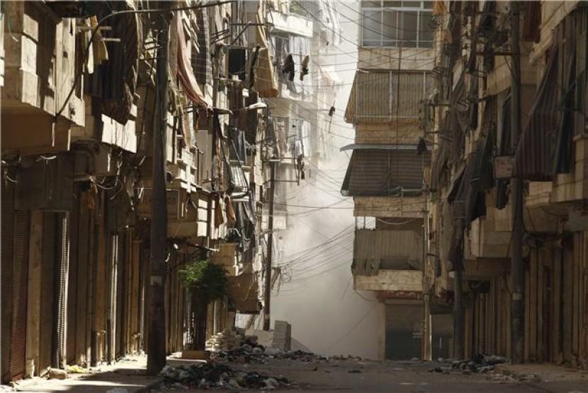 Asap mengepul di antara gedung di Distrik Salah Edinne, Aleppo, Suriah, setelah tentara pemerintah terlibat adu tembak dengan gerilyawan.