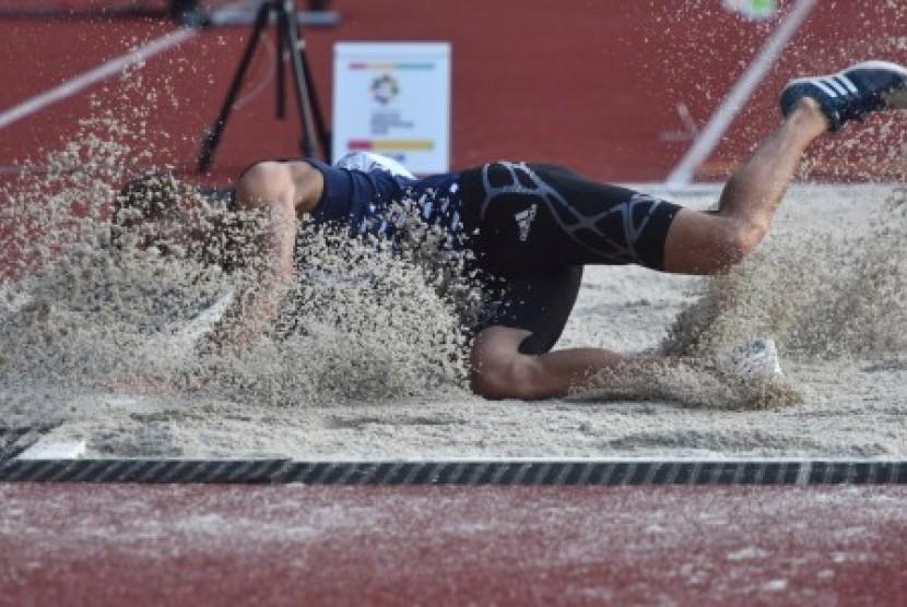 Atlet mendarat di bak pasir pada perlombaan lompat jauh di Stadion Utama Gelora Bung Karno, Senayan, Jakarta.