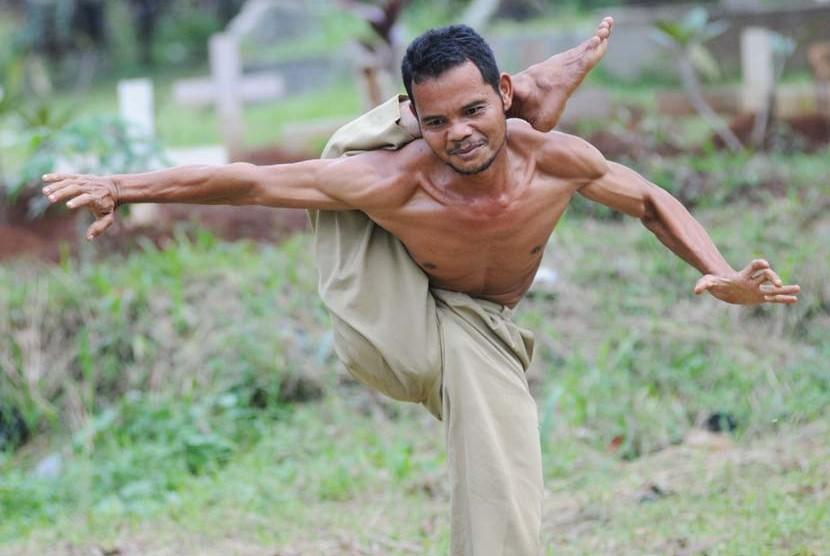 Atraksi Syarifudin alias Udin Karet warga Desa Tengah, Cibinong, Kabupaten Bogor, Jawa Barat, Rabu (11/4) saat melatih kemampuan kelenturan tubuhnya.