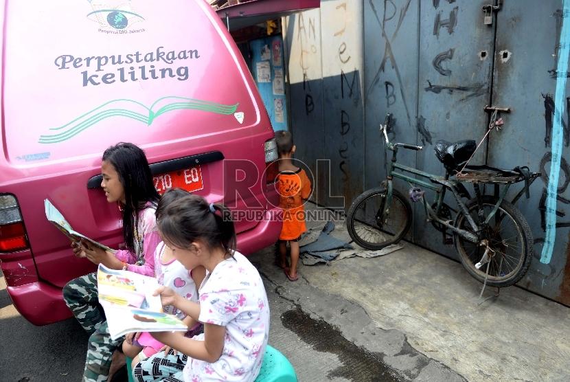 Beberapa anak membaca di perpustakaan keliling di Jakarta, Ahad (27/9).