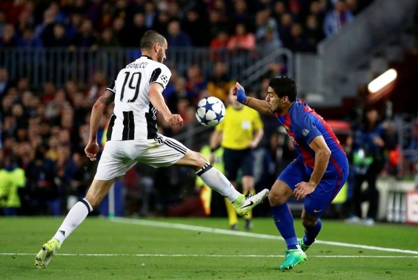 Bek Juventus Leonardo Bonucci (kiri) saat menahan upaya serangan penyerang Barcelona Luis Suarez.
