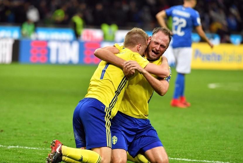 Bek Timnas Swedia, Andreas Granqvist (kanan) dan Sebastian Larsson merayakan keberhasilan timnya lolos ke putaran final Piala Dunia 2018 usai menahan imbang Italia 0-0 di leg kedua babak kualifikasi Zona Eropa di Stadion Giuseppe Meazza, Milan, Italia, Senin (13/11).