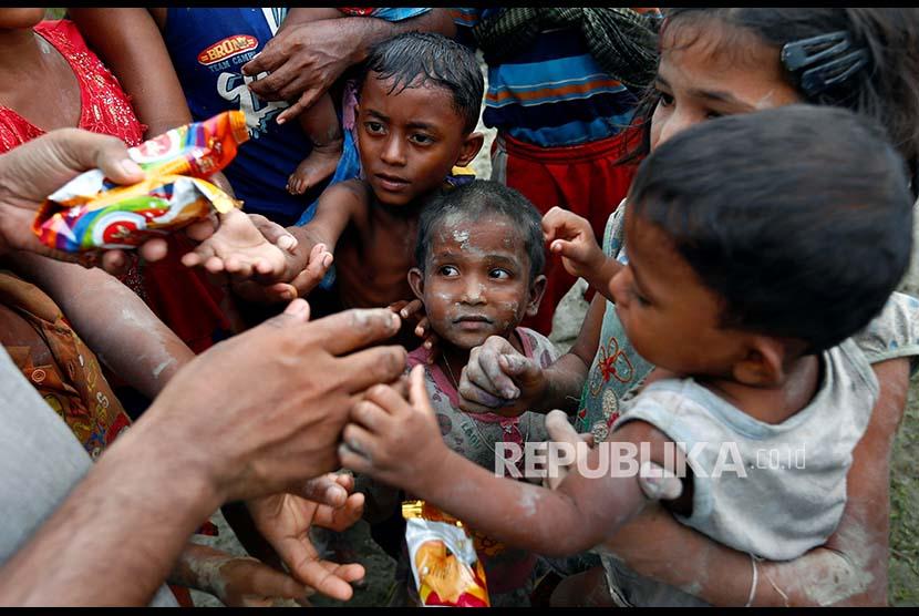 Bocah pengungsi Rohingya berbagi makanan setelah melintasi pesawahan setelah melintasi perbatasan Bangladesh-Myanmar di Teknaf, Bangladesh, Rabu (6/9).