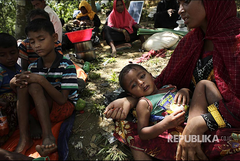 Rohingya boy in refugee camp with other refugees sheltering in a tree in Ukhiya, Cox's Bazaar, Bangladesh.