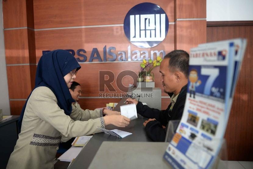 BPRS Satu Kompartemen: Karyawan melayani nasabah di Bank Perkreditan Rakyat Syariah (BPRS) Al Salaam, Jakarta, Rabu (22/4). (Republika/ Yasin Habibi.)
