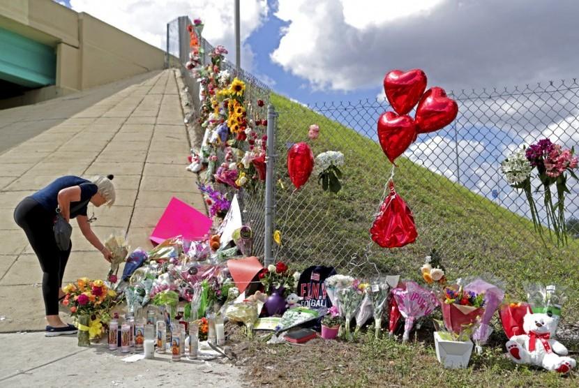 Bunga, balon-balon dan boneka di Marjory Stoneman Douglas High School di Parkland, Florida menjadi simbol untuk mengingat korban penembakan di sekolah tersebut, Ahad (18/2).