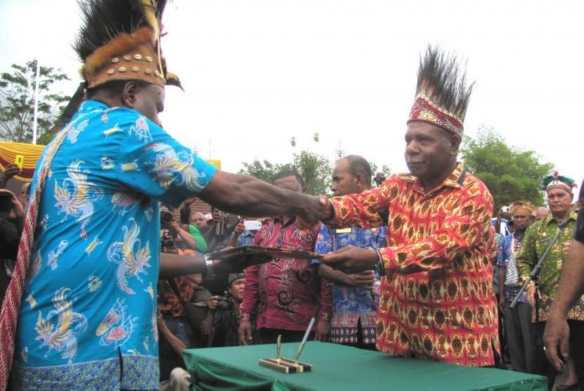 Bupati Jayapura Mathius Awoitouw (kanan) menyerahkan peraturan bupati tentang pengakuan dan perlindungan masyarakat adat di Kabupaten Jayapura kepada wakil masyarakat adat.