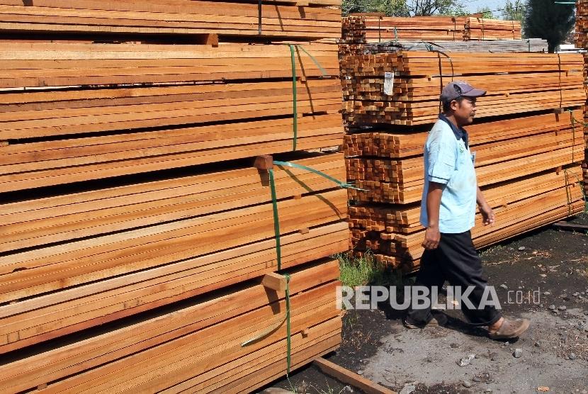 Buruh mengecek tumpukan bahan pengolahan kayu di Jakarta.