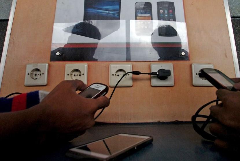 Calon penumpang kereta menggunakan fasilitas tempat pengisian baterai (charger) telepon selular di Stasiun Tasikmalaya, Jawa Barat, Kamis (9/7).