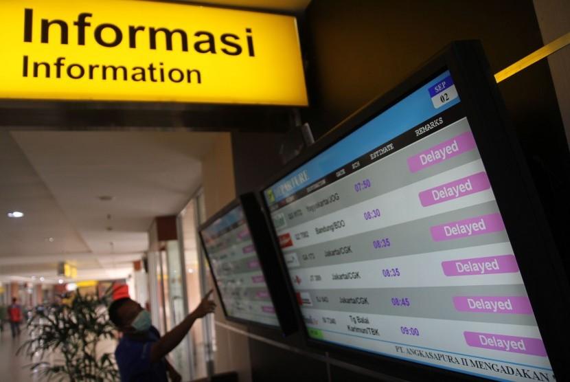 Calon penumpang melihat monitor informasi yang menunjukkan sejumlah penerbangan yang ditunda (Delayed) di Bandara Sultan Syarif Kasim II Pekanbaru, Riau, Rabu (2/9).
