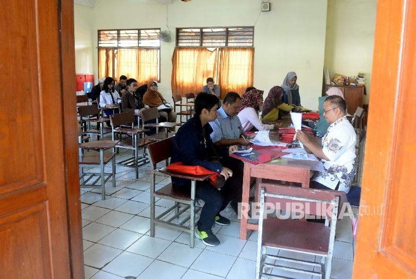 Calon siswa dan Orang tua wali melakukan pendaftaran ulang sebelum kegiatan belajar mengajar di SMA 6 Depok, Jawa Barat, Rabu (12/7).