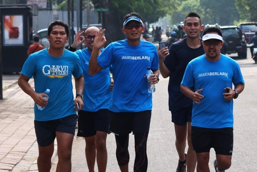 Calon Wakil Gubernur DKI Jakarta nomor urut tiga, Sandiaga Uno (tengah) berlari menuju Polsek Tanah Abang saat akan menjalani pemeriksaan di Jakarta, Jumat (17/3).