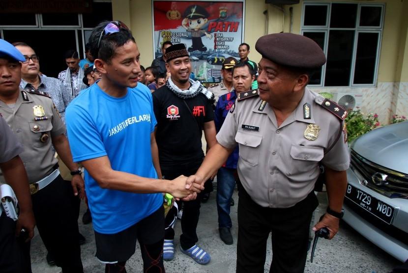 Calon Wakil Gubernur DKI Jakarta nomor urut tiga, Sandiaga Uno (kiri) meninggalkan kantor polisi usai menjalani pemeriksaan di Polsek Tanah Abang, Jakarta, Jumat (17/3).