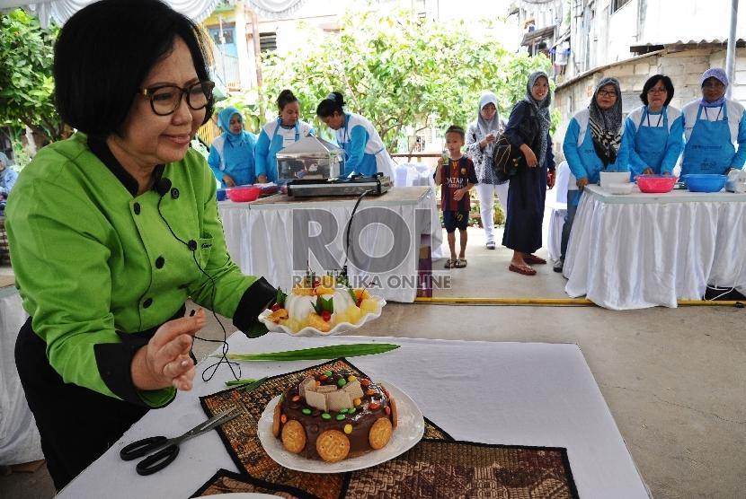 Chef Sisca Soewitomo memberikan arahan kepada ibu rumah tangga saat belajar memasak di Rusun Buaran, Jakarta, Selasa (14/9).