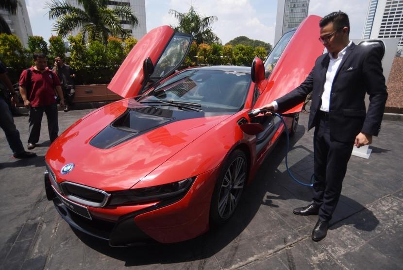 Corporate Communication Specialist BMW Group Indonesia Ismail Ashlan mengisi bahan bakar listrik mobil BMW i8 Protonic Red Edition yang merupakan edisi terbatas disela penyerahan mobil tersebut kepada pelanggan di Jakarta, Kamis (20/4).