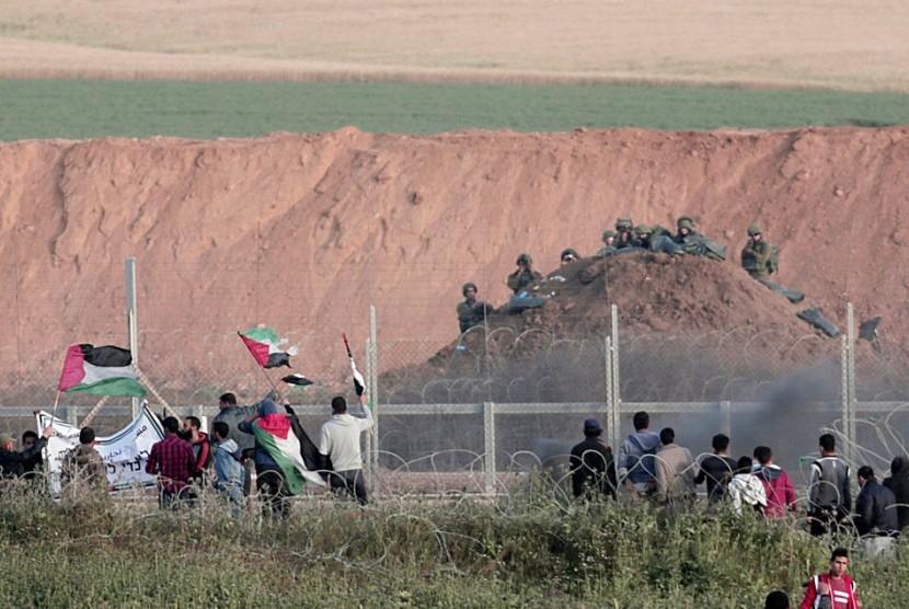 Demonstran Palestina melambaikan bendera di hadapan tentara Israel di perbatasan Gaza-Israel dekat Beit Lahiya, Rabu, 4 April 2018.