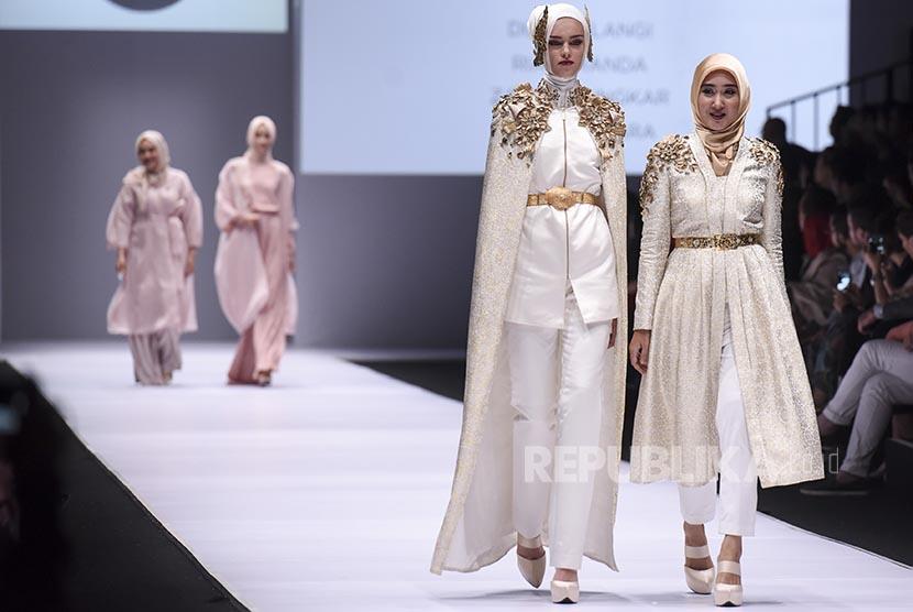 Desainer Dian Pelangi (kanan) berjalan bersama modelnya saat pembukaan acara Jakarta Fashion Week 2017 di Senayan City, Jakarta, Sabtu (22/10). Acara tahunan yang berlangsung hingga Jumat (28/10) tersebut akan menghadirkan karya dari 250 desainer dan label