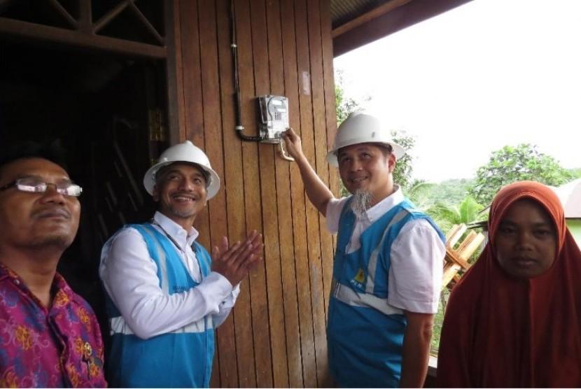 Direktur Bisnis PLN Regional Kalimantan, Machnizon (ketiga dari kiri), menyalakan meteran listrik milik seorang warga di Desa Bukit Merdeka, Kecamatan Samboja, Kutai Kartanegara, Kalimantan Timur, Kamis (26/4). PLN menargetkan seluruh desa di Kaltim dan Kaltara bakal teraliri listrik pada 2018 ini.