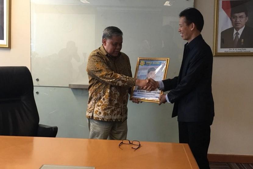 Direktur BSI, Naba Aji Notoseputro (kanan) menyerahkan cindera mata kepada Direktur Jendral Kelembagaan Dikti Patdono Suwigno.