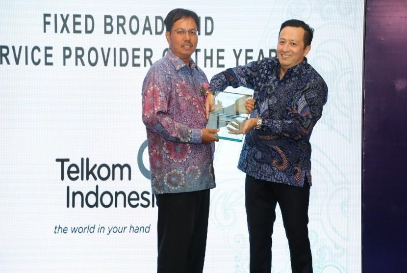 Direktur Consumer Service Telkom Mas'ud Khamid (kiri) dan Managing Director and Head of Emerging Markets Frost & Sullivan Hazmi Yusof (kanan) saat menyerahkan award Indonesia Fixed Broadband Service Provider of the Year & Indonesia Telecom Service Provider of the Year kepada Telkom di Jakarta, Selasa (28/11).