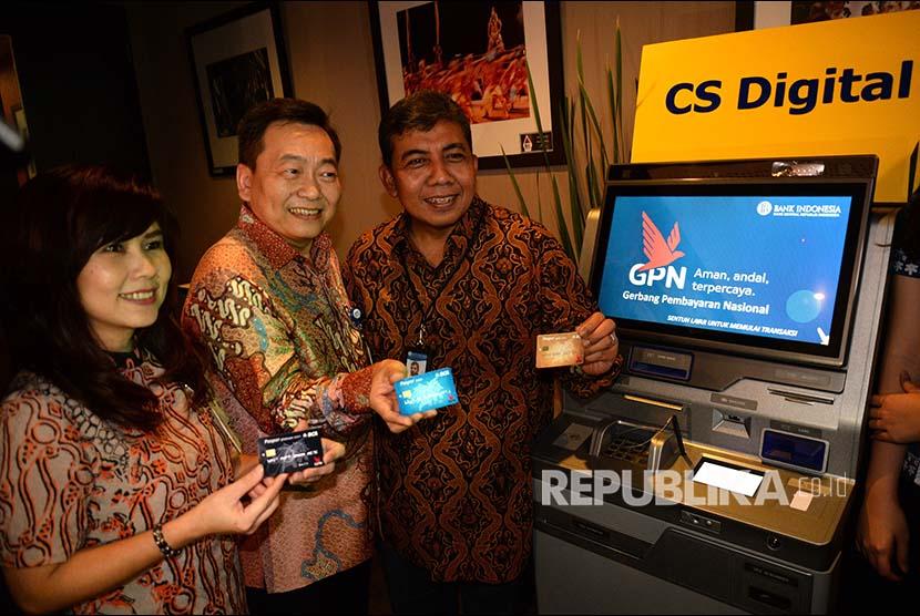Direktur DKSP Bank Indonesia Punky P Wibowo bersama Direktur BCA Santoso, dan Direktur BCA Lianawaty Suwono menunjukan Kartu Paspor BCA berlogo Gerbang Pembayaran Nasional ( GPN) di Jakarta, Senin (16/4). Untuk tahap awal, BCA akan menerbitkan sebanyak 2 juta kartu debit berlogo Garuda.