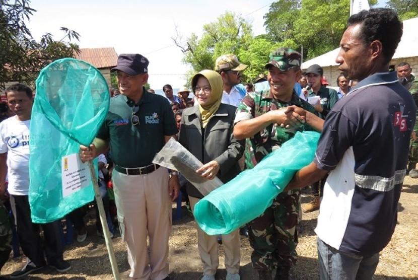 Direktur Human Capital Management PT PLN Muhamad Ali (kiri, bertopi) didampingi Direktur Medik dan Keperawatan RSCM Ratna Dwi Restuti (berjilbab) memberikan beragam bantuan kepada masyarakat Pulau Liran,  Kabupaten Maluku Barat Daya Rabu (20/9) lalu