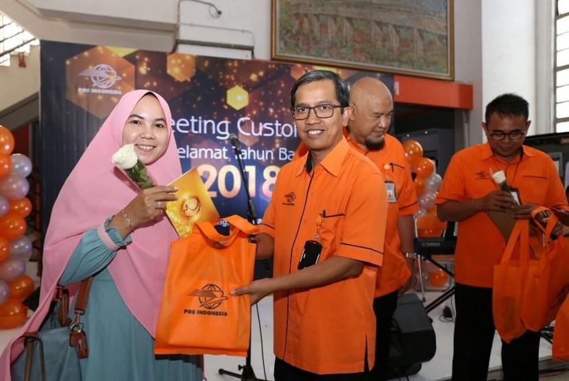 Direktur Jasa Keuangan PT Pos Indonesia Ihwan Sutardiyanta menyerahkan souvenir kepada pelanggan pertama yang datang ke Kantor Pos pusat di Kota Bandung, Selasa (2/1). Mengawali kegiatan di 2018, direksi PT Pos Indonesia menggelar kegiatan sapa pelanggan dan karyawan.