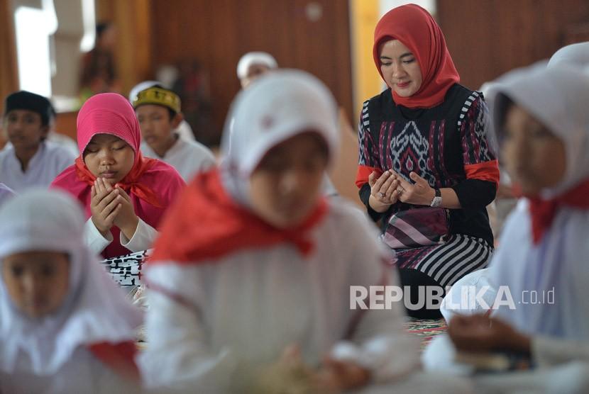 Direktur SDM Pertamina Nicke Widyawati (kanan) berdoa bersama dengan sejumlah anak yatim peserta acara Khataman Alquran di Kantor Pusat Pertamina, Jakarta, Kamis (7/12).