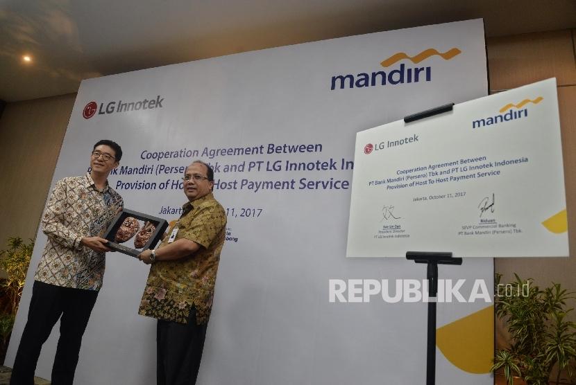 Direktur Utama LG Innotek Indonesia Bae Un Gyo (kiri), memberikan cinderamata kepada Senior EVP Commercial Banking Bank Mandiri Riduan seusai penandatanganan perjanjian kerjasama layanan perbankan di Jakarta, Rabu (11/10).