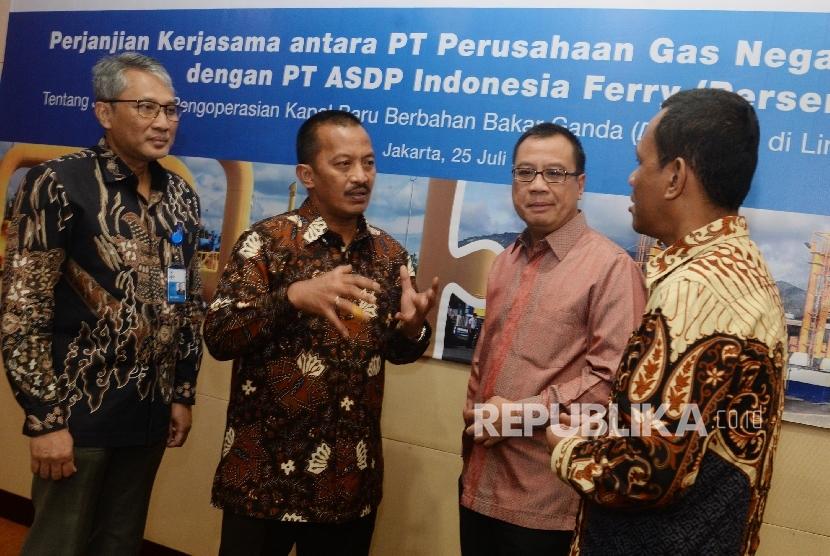 Direktur Utama PT Perusahaan Gas Negara (Persero) Tbk (PGN) Jobi Triananda Hasjim (kedua kiri), Direktur Utama PT ASDP Indonesia Ferry Fahmi (kedua kanan), Direktur Strategi Bisnis dan Pengembangan PGN Gigih Prakoso (kiri), dan Direktur Teknik dan Operasional ASDP La Mane seusai penandatanganan Perjanjian Kerja Sama Joint Study Pengoperasian Kapal Baru Berbahan Bakar Ganda (Dual Fuel) di Lintasan Merak-Bakauheni di Kantor Pusat PGN, Jakarta Pusat, Selasa (25/7).