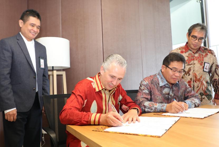 Direktur Utama Telkom Alex J. Sinaga (kedua dari kanan) dan Presiden Direktur Telstra Andrew Penn (kedua dari kiri) menandatangani nota kesepahaman pembentukan Global Delivery Center (GDC) di Indonesia yang disaksikan oleh Direktur Enterprise & Business Service Telkom Dian Rachmawan (paling kiri) dan Direktur Digital & Strategic Portfolio Telkom David Bangun (paling kanan) di Jakarta, Rabu (31/1).