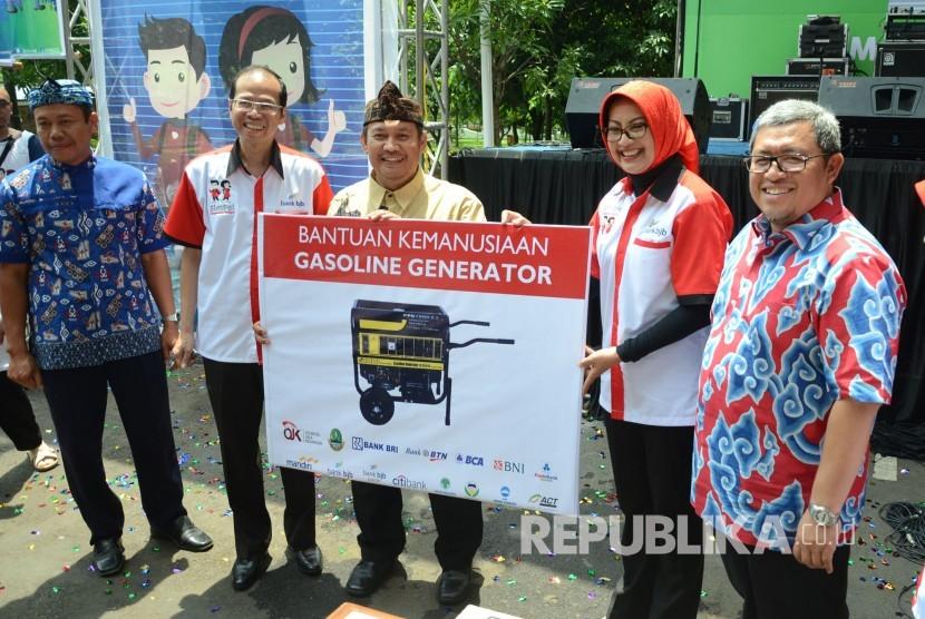 Dirut Bank BJB Ahmad Irfan (kedua kiri) bersama pejabat lainnya memberikan bantuan kepada masyarakat