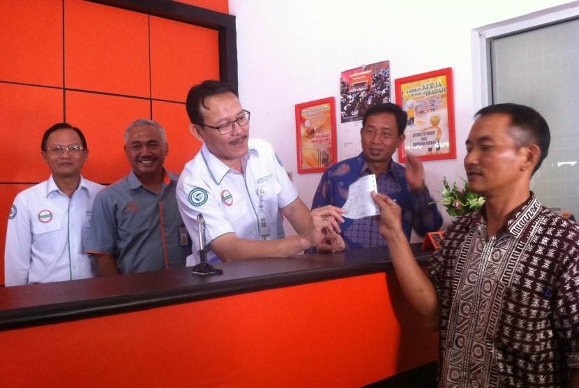 Dirut BPJS Kesehatan Fachmi Idris (tengah) menyerahkan bukti pembayaran dengan sistem payment point online bank (PPOB) di Kantor Pos Congeang, Kabupaten Sumedang, belum lama ini.