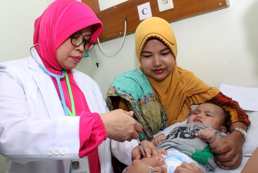 Dokter menyuntikkan vaksin kepada balita yang terpapar vaksin palsu saat melakukan vaksinasi ulang, di rumah sakit Rawalumbu, Bekasi, Jawa Barat, Selasa (26/7).