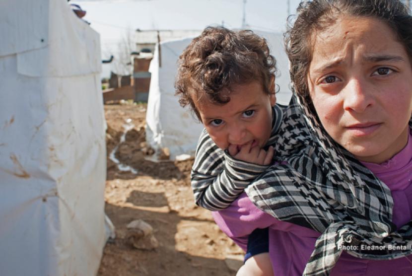 Dua anak Suriah di antara tenda-tenda pengungsian. Perang saudara telah membuat penduduk negara itu menderita.
