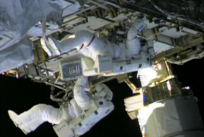 Dua astronot dari stasiun antariksa NASA, Chris Cassidy (atas) dan Tom Marshburn bekerja memperbaiki kebocoran di stasiun tersebut