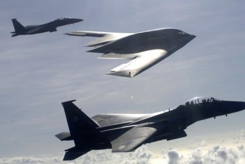 Dua jet tempur F-15 E Eagle bersama pesawat pengebom B-2 dalam formasi udara.