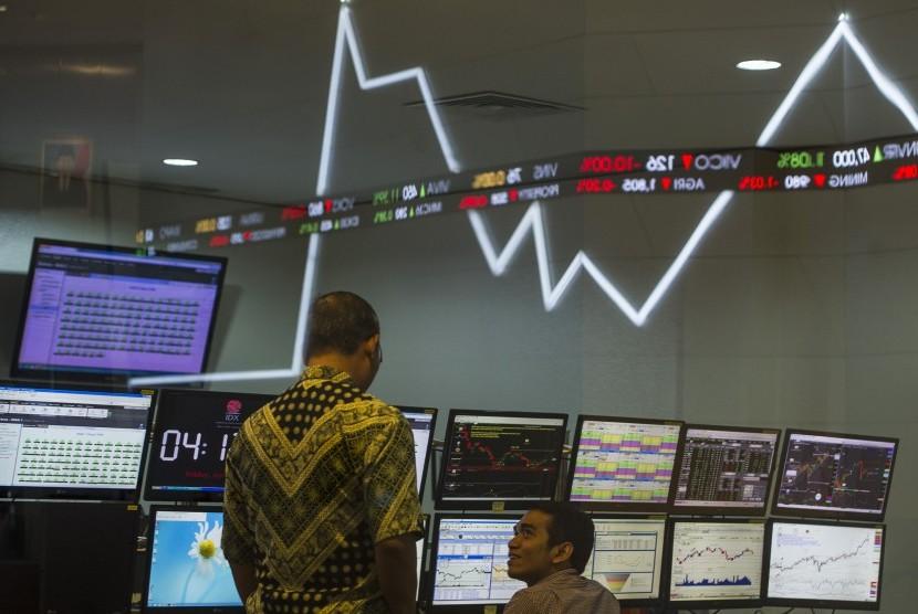 Dua karyawan mengamati pergerakan Indeks Harga Saham Gabungan (IHSG) di Bursa Efek Indonesia, Jakarta, Jumat (22/4).