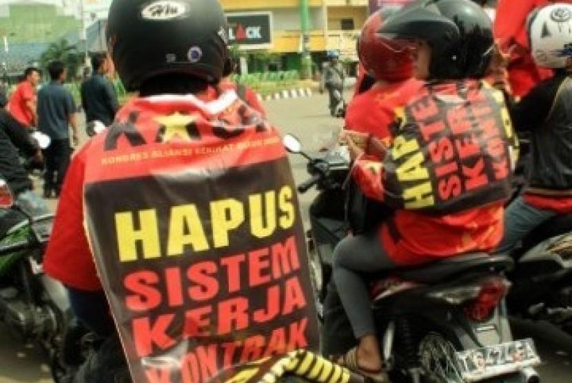 Dua orang buruh yang tergabung dalam Federasi Serikat Pekerja Karawang menempelkan poster berisi tuntutan menghapus sistem kerja kontrak pada kaosnya, saat unjuk rasa memperingati Hari Buruh Internasional, di Bundaran Mega M, Karawang, Jabar, Minggu (1/5).