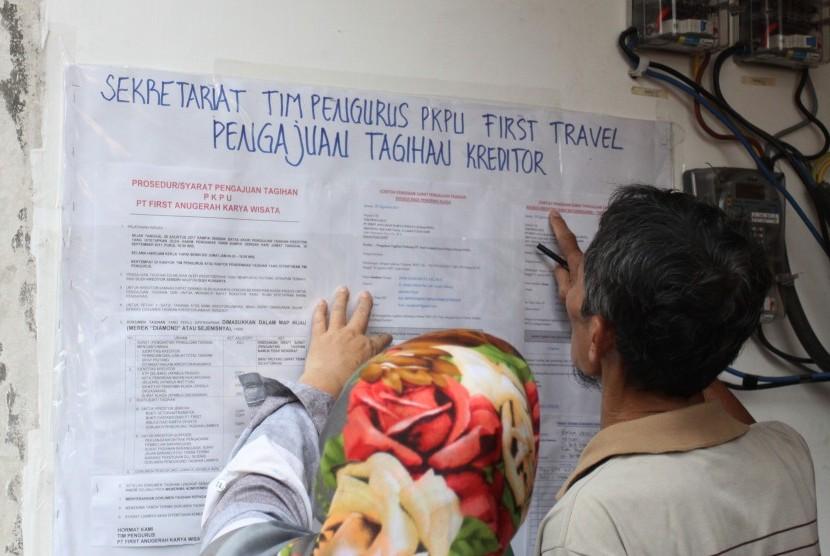 Dua orang korban penipuan First Travel melihat nama pada daftar di kantor tim pengurus penundaan kewajiban pembayaran utang (PKPU) di Grand Wijaya Center, Jakarta, Jumat (8/9).