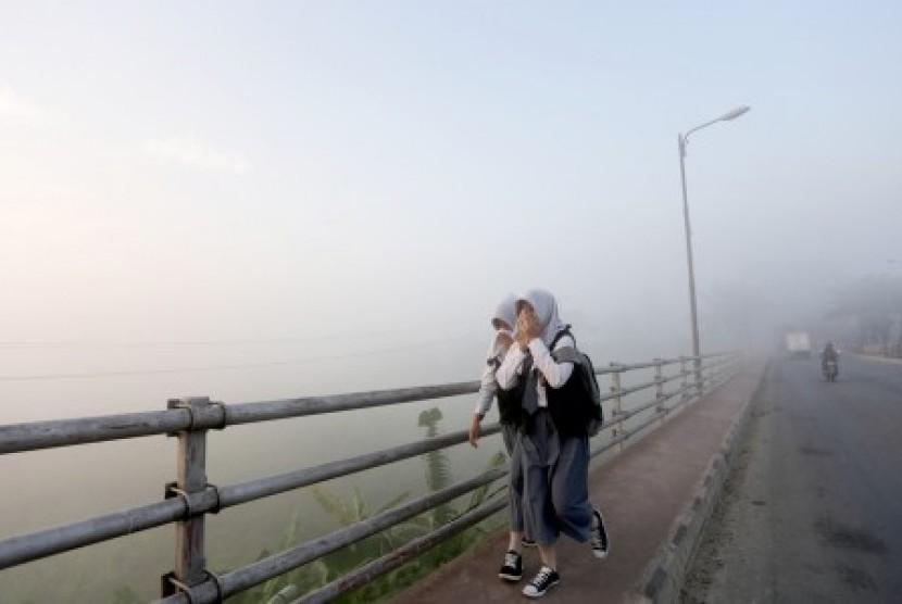 Dua orang siswa pelajar melewati kabut asap yang menutupi di jembatan Musi II, Palembang. Sumsel. Senin (31/8).