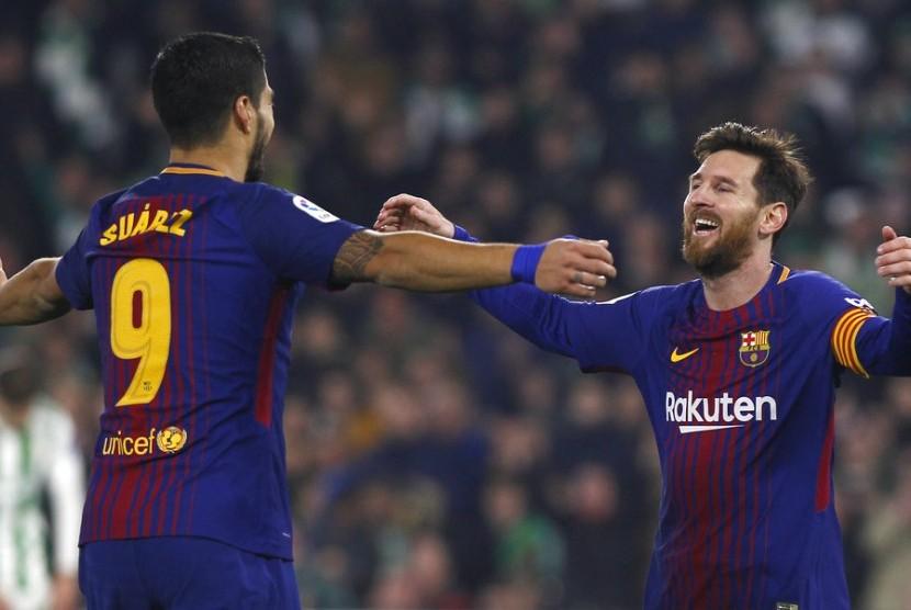 Dua striker Barcelona, Lionel Messi (kanan) dan Luis Suarez merayakan gol ke gawang Real Betis pada laga La Liga di stadion Villamarin, Senin (21/1). Barce menang 5-0.