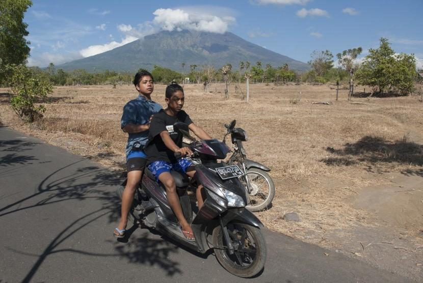 Dua warga di jalan Desa Datah yang berjarak sekitar 10 kilometer dari Gunung Agung yang berstatus awas di Karangasem, Bali, Selasa (26/9).